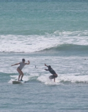 Sarah catching a wave with a wave to Pollo